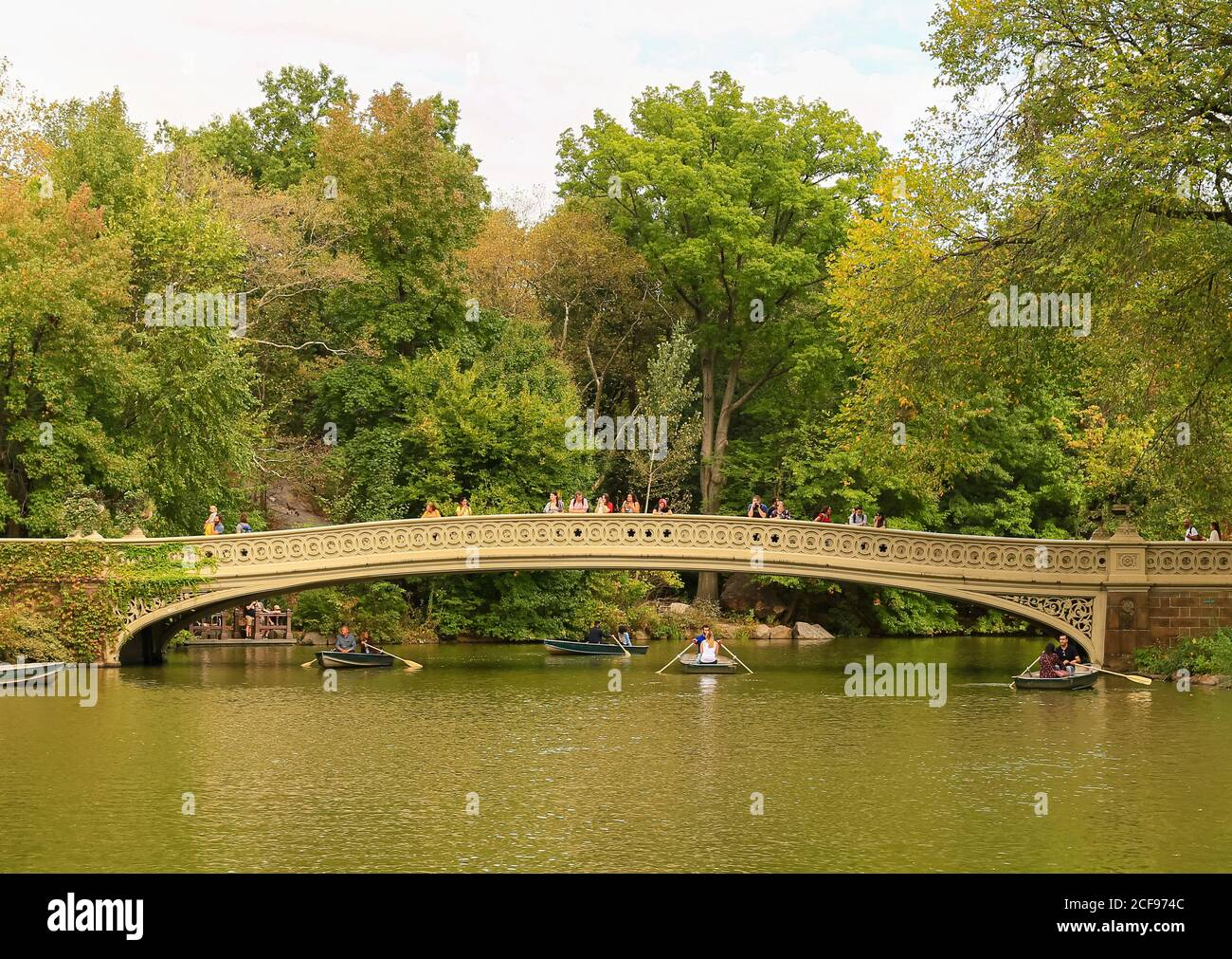 New York City, USA - October 7, 2019: The Bow Bridge in Central Park. Pepole walking across the bridge or looking in the lake. Rowing boats are under Stock Photo