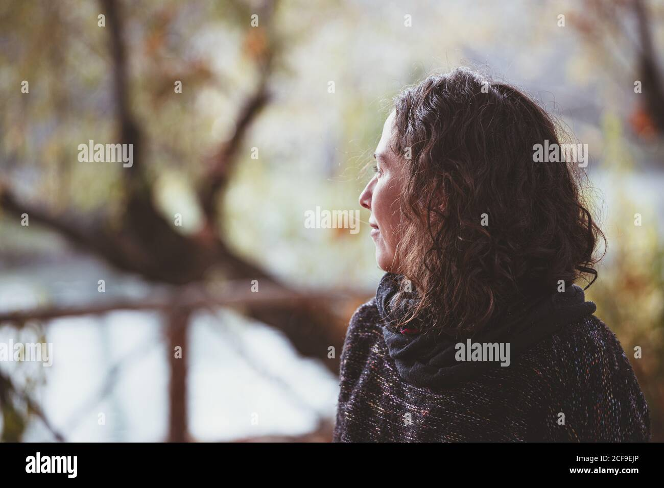 Adult lady with curly hair looking away and thinking while standing on blurred background of peaceful autumn park Stock Photo