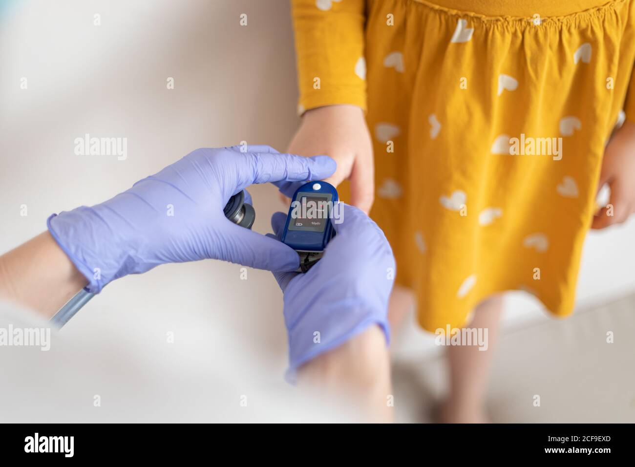 From above view of anonymous doctor in latex gloves using finger cuff to examine blood pressure of little girl in casual yellow dress Stock Photo