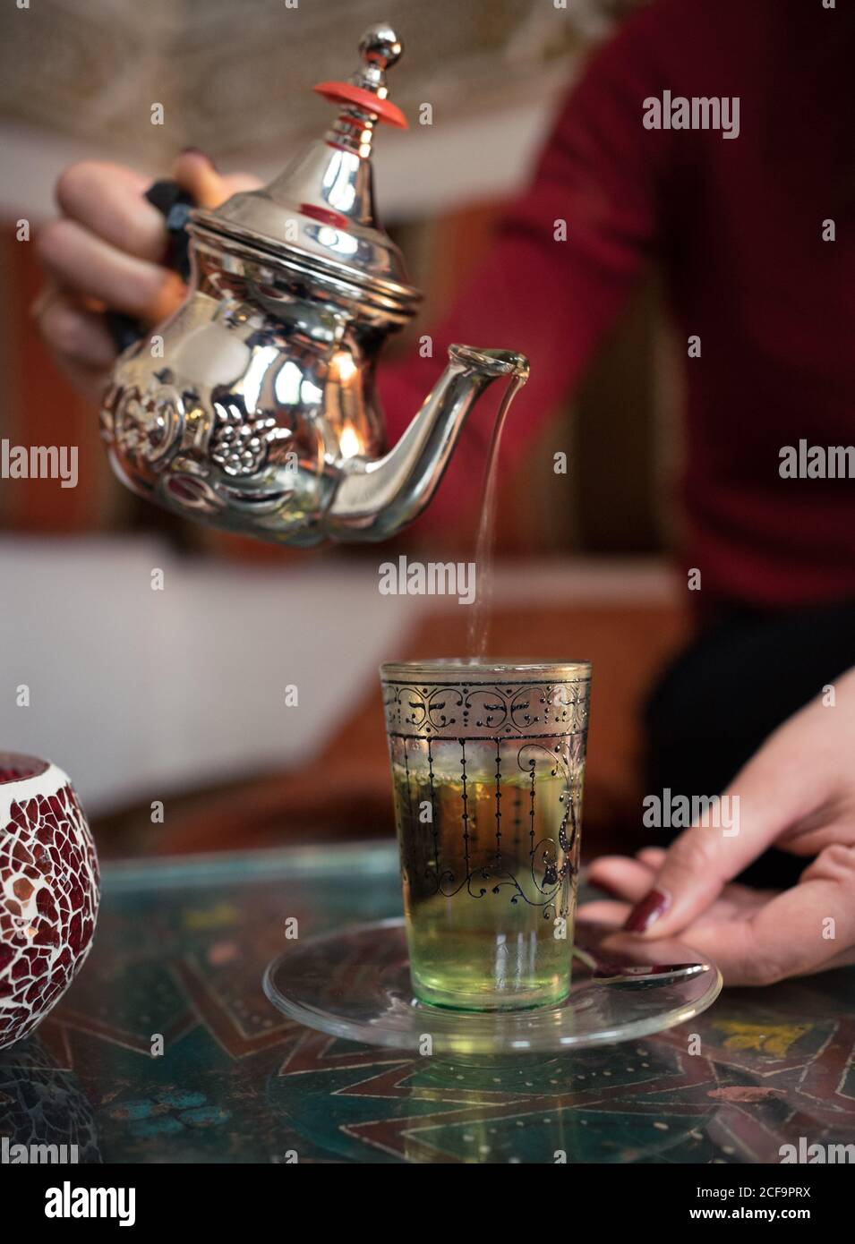Happy ethnic female pouring fresh Arabic tea in cup while sitting on comfortable couch in small ornamental room Stock Photo