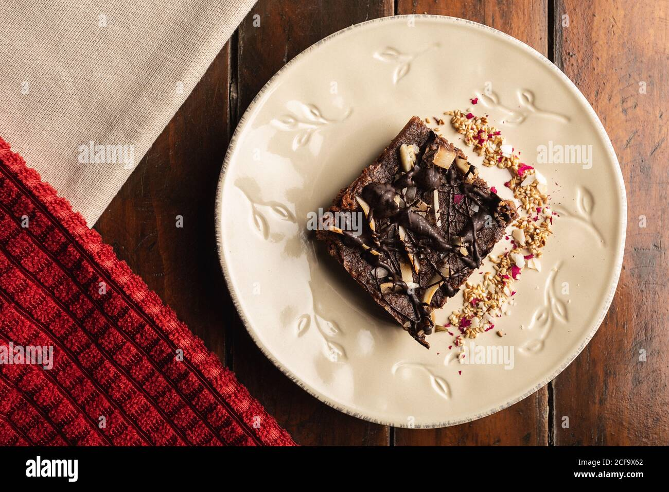 From above appetizing fragrant brown cake with oat flakes in white decorated plate on wooden background Stock Photo