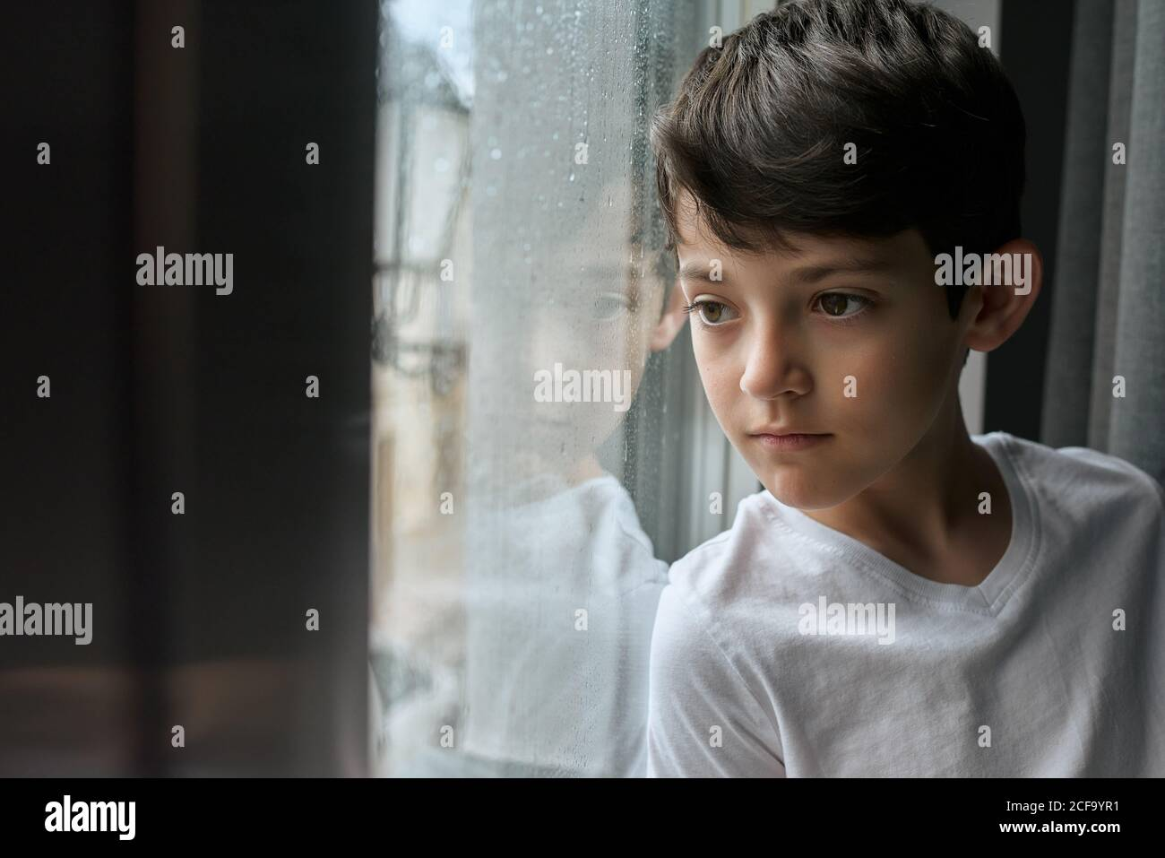 Bored child in casual clothing standing in living room and leaning on window while observing rain on street Stock Photo
