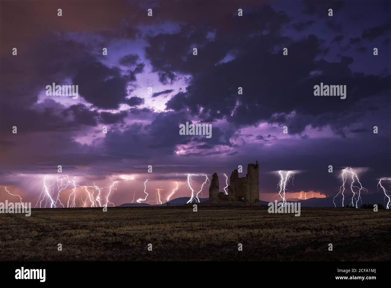 Amazing scenery of lightning storm on colorful cloudy sky over ruined old castle at night Stock Photo