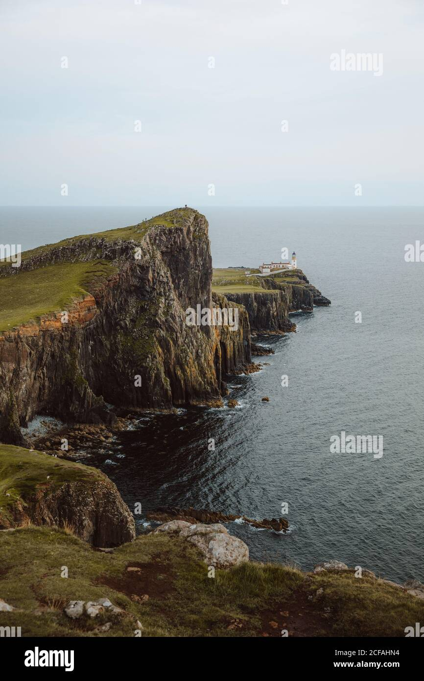 From above majestic view of Neist Point Lighthouse built on high rocks surrounded by dark water on daytime Stock Photo