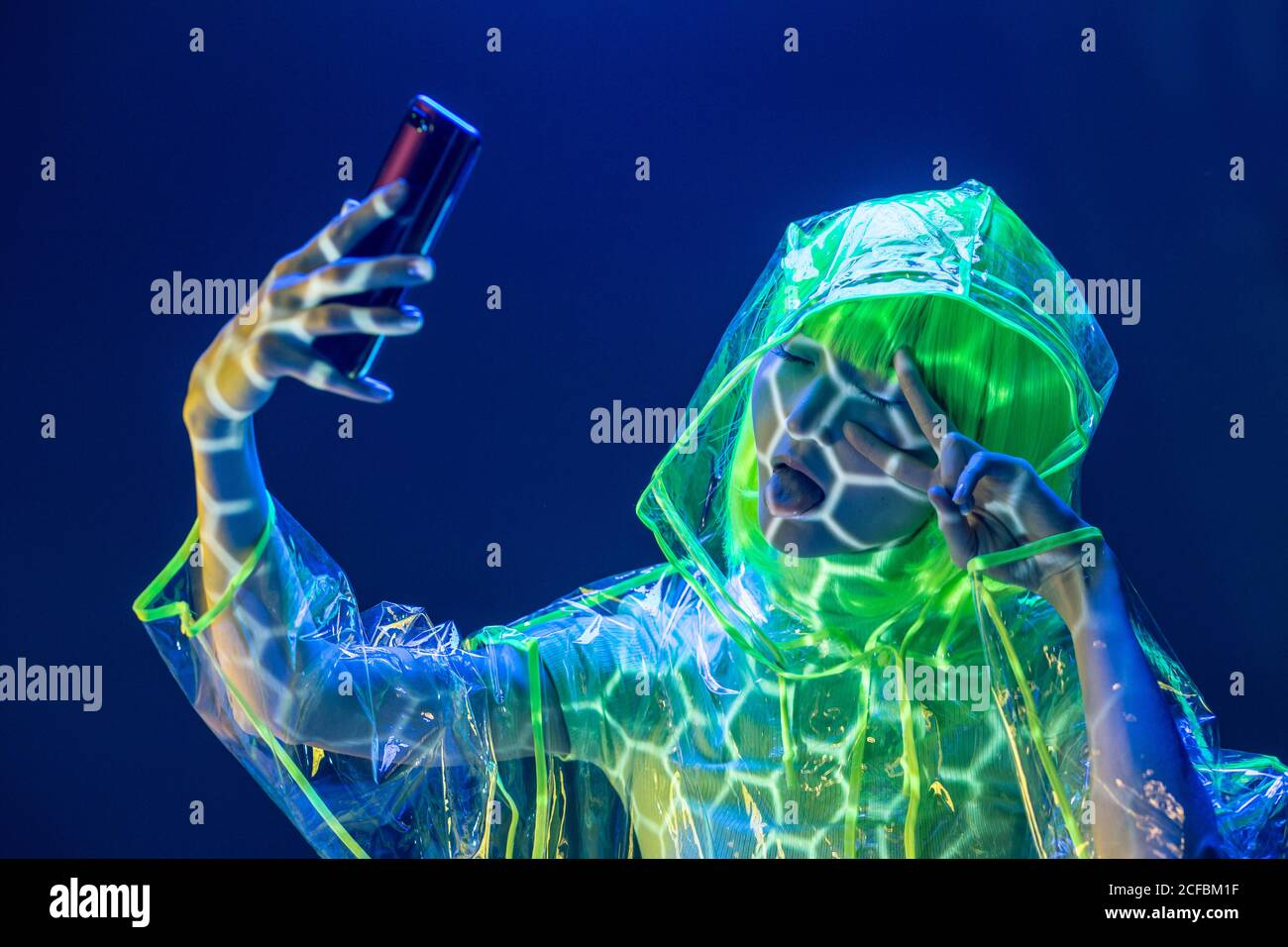 Young Asian woman in futuristic wear and green wig taking selfie on smartphone in fluorescent light Stock Photo