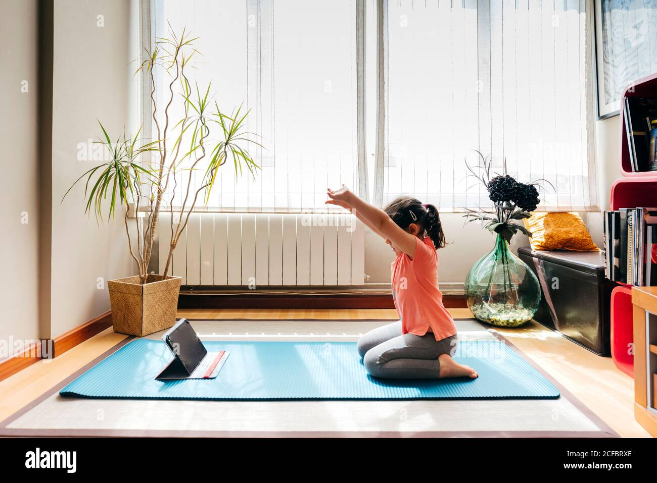 Side view of positive little girl sitting on her knees in yoga pose on mat near window at home while practicing yoga and watching video tutorials on tablet Stock Photo