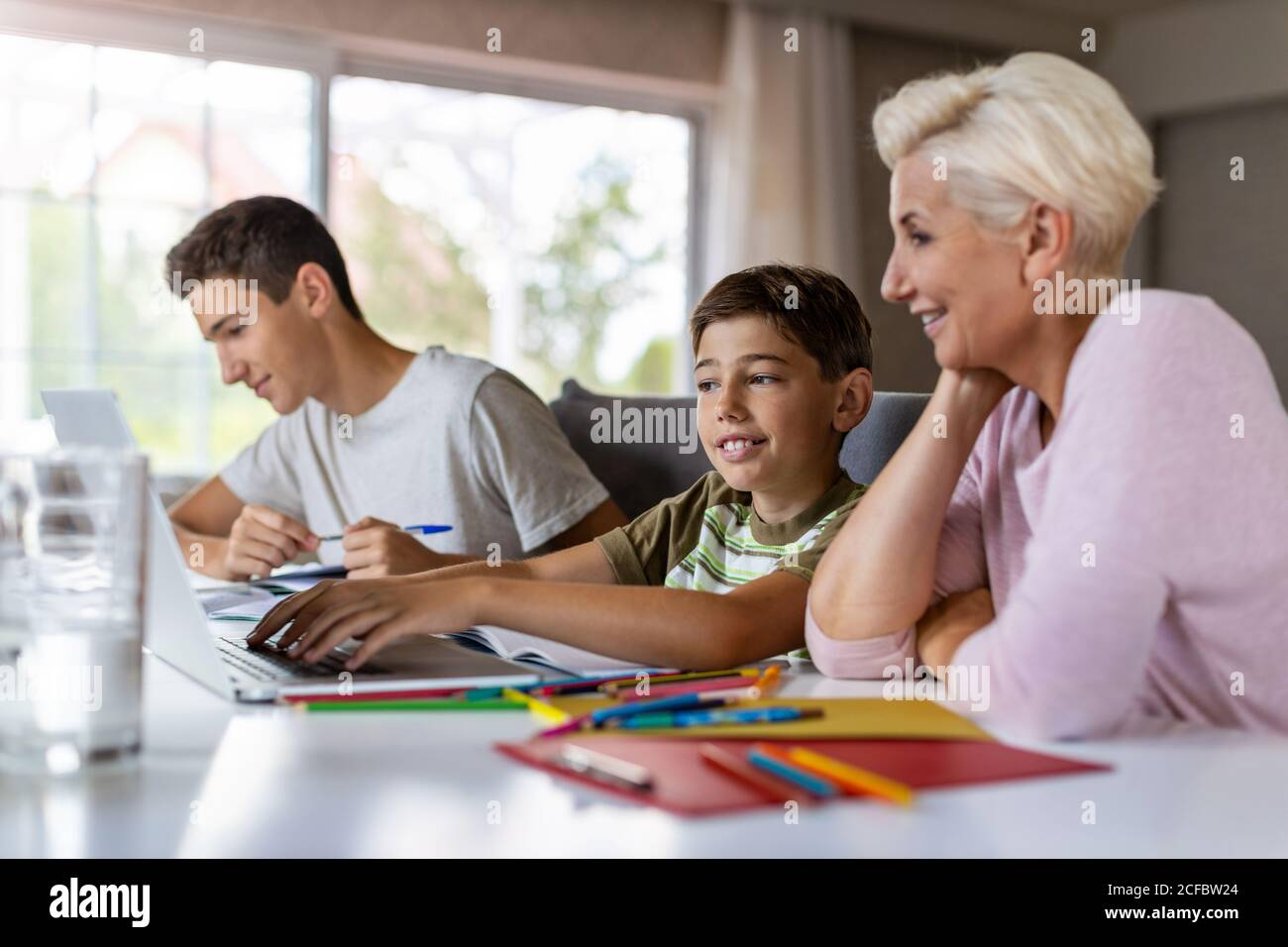 Mother helping her kids doing homework at home Stock Photo