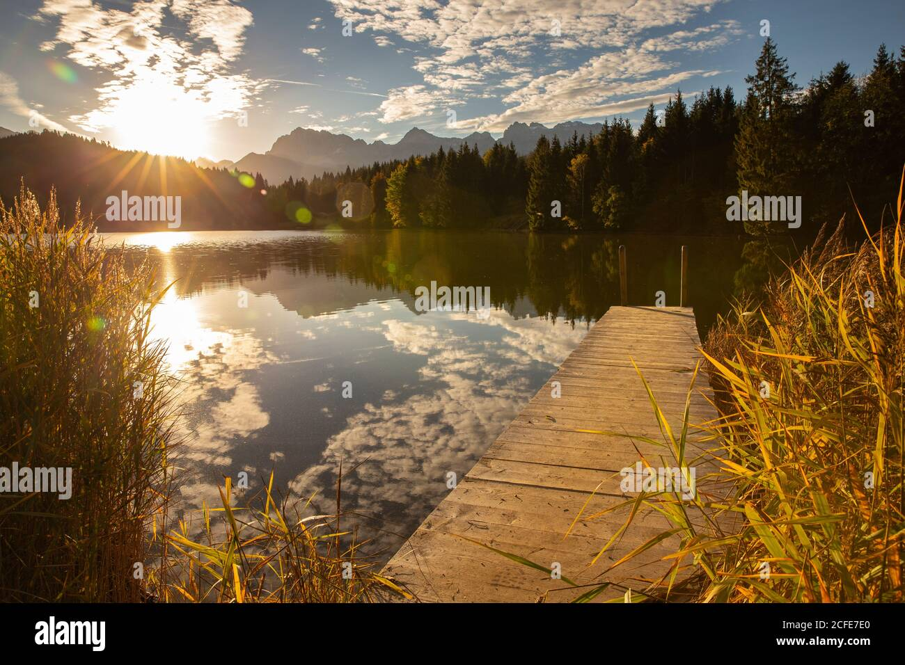 View from Badesteg near Geroldsee towards the Karwendel mountains at sunrise, blue sky, water reflection, sun rays, trees, reeds, clouds, Krün, Stock Photo