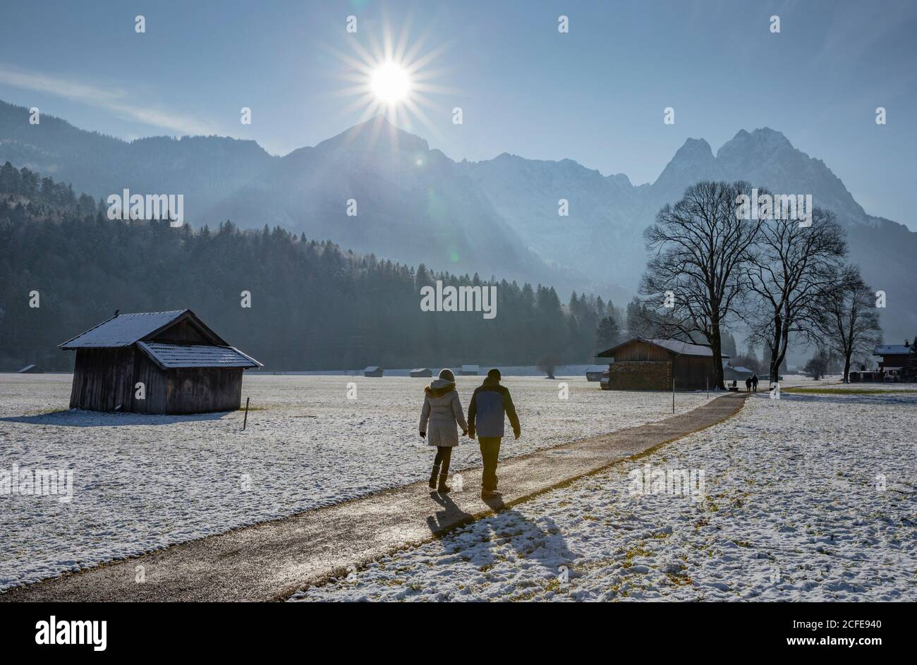 Man and woman on a winter walk on a dirt road in Garmisch-Partenkirchen, looking towards the Wetterstein Mountains with the Alpspitze and wax stones, Stock Photo