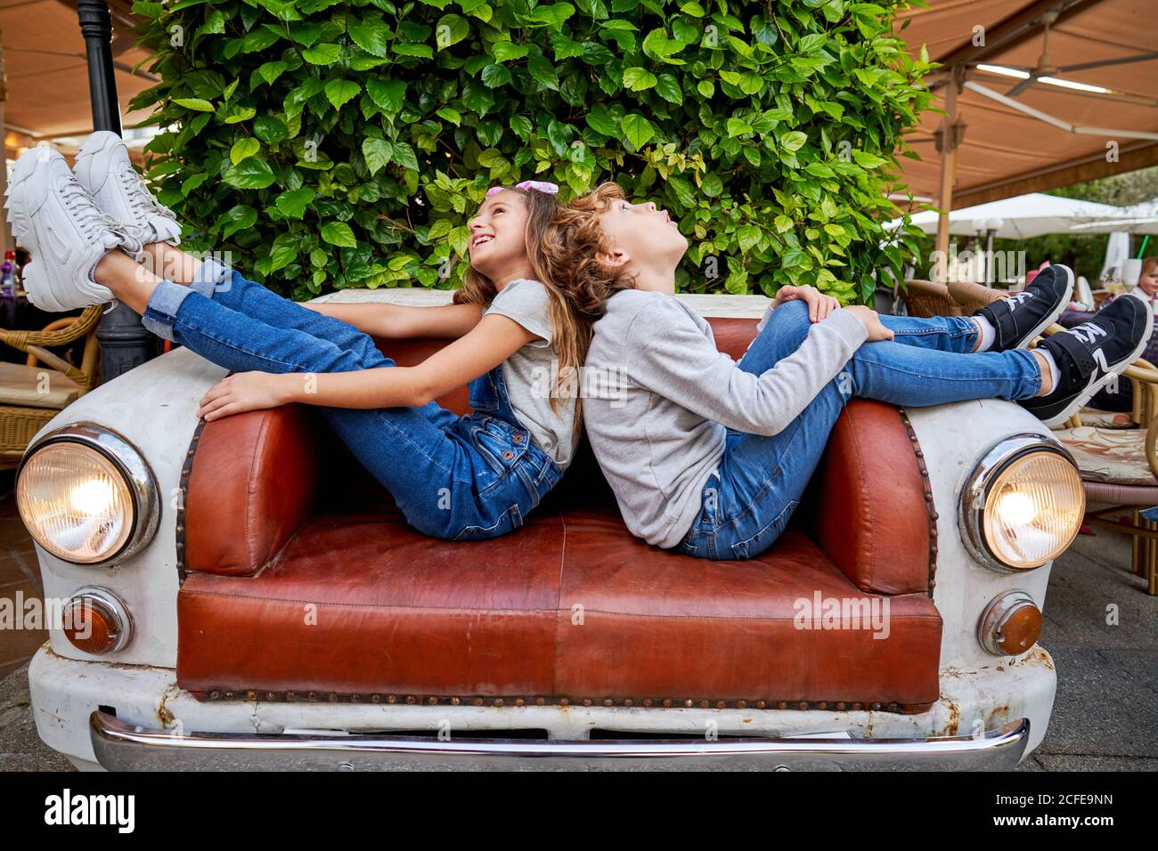 Side view of young lively children sitting back to back with legs up on car front converted into couch and looking upwards to ceiling while smiling and wondering Stock Photo