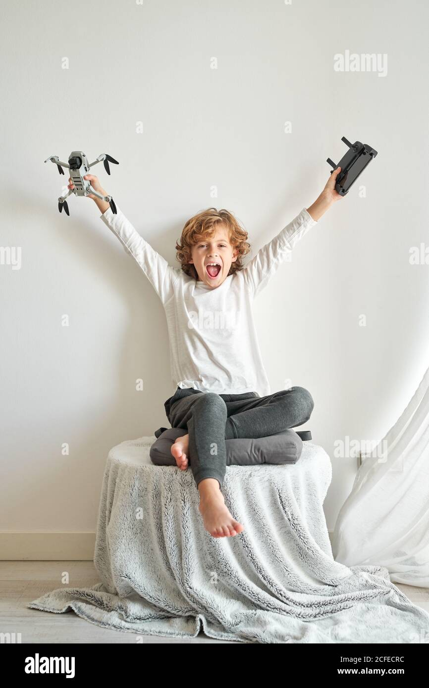 Child manipulating a drone and the remote control just given to him Stock Photo