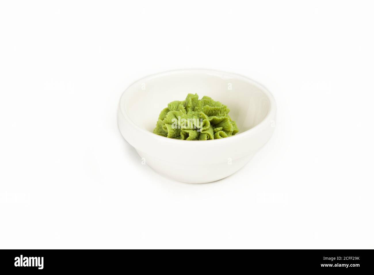 Bowl with wasabi sauce on a white plate. For the restaurant menu. Traditional Chinese classic wasabi seasoning platter. Japanese cuisine horseradish pasta. Stock Photo