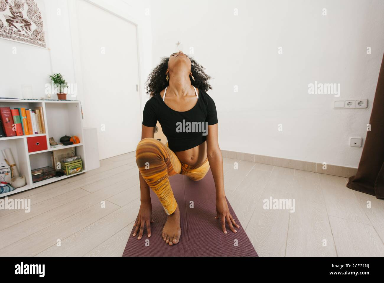anonymous African American attractive young woman sitting in yoga pose with closed eyes on mat in light room Stock Photo