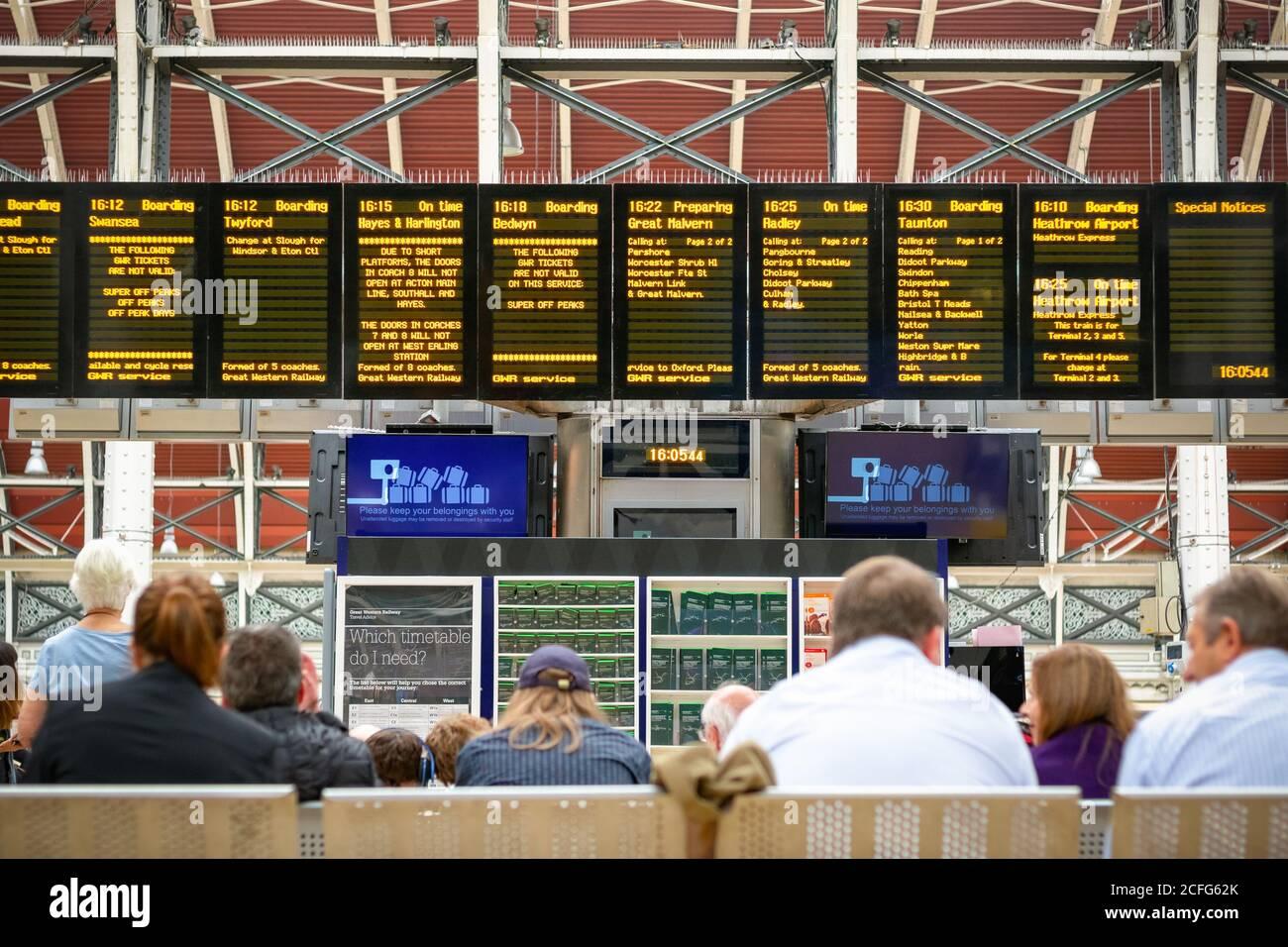 Unrecognised passengers checking train timetable at London Paddington railway station Stock Photo