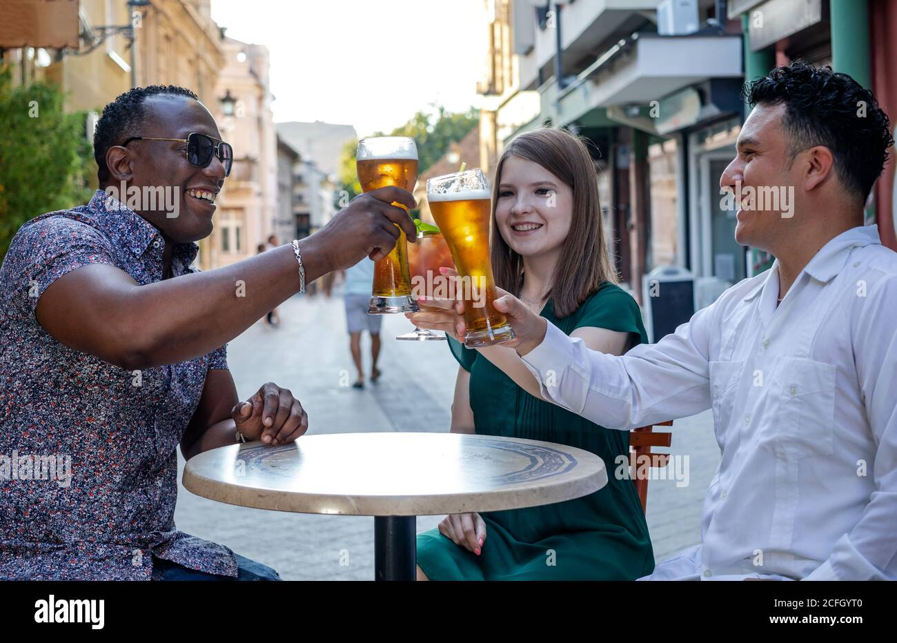 Multiracial group of friends drinking and toasting at street terrace of the cafe. Friendship concept with young multi ethnic people enjoying time toge Stock Photo