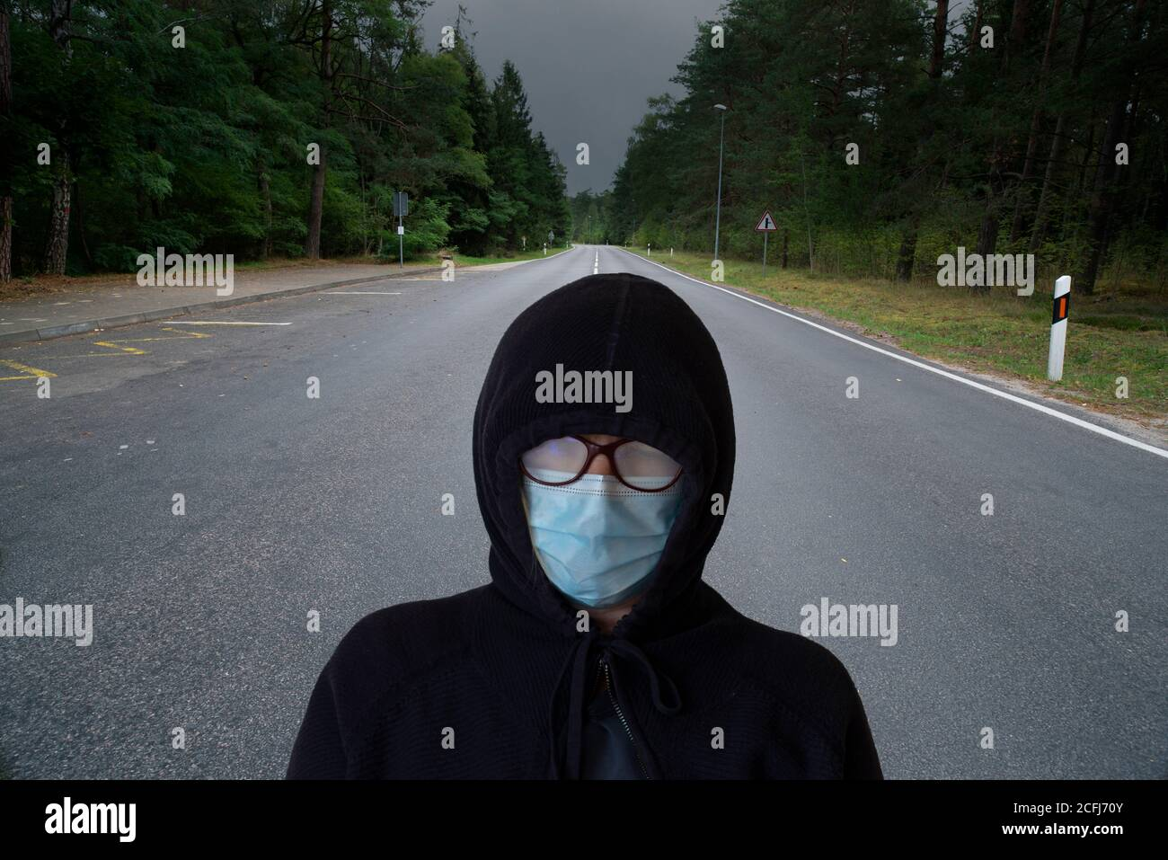 A woman with a protective mask is standing in the middle of the road. Concept of a long road to recovery. Stock Photo