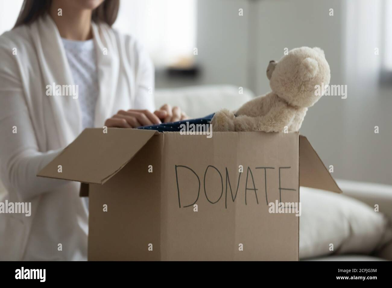 Kind volunteer put things for poor families in charity package. Stock Photo