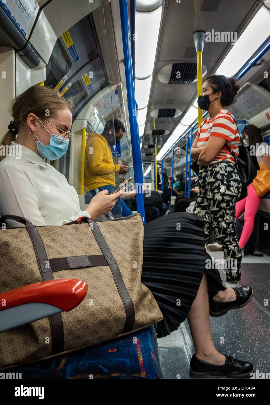 Passengers on the London Underground train carriage wearing face covering and trying to practice social distancing. Stock Photo