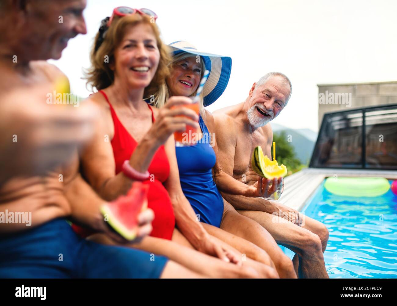 Group of cheerful seniors sitting by swimming pool outdoors in backyard. Stock Photo