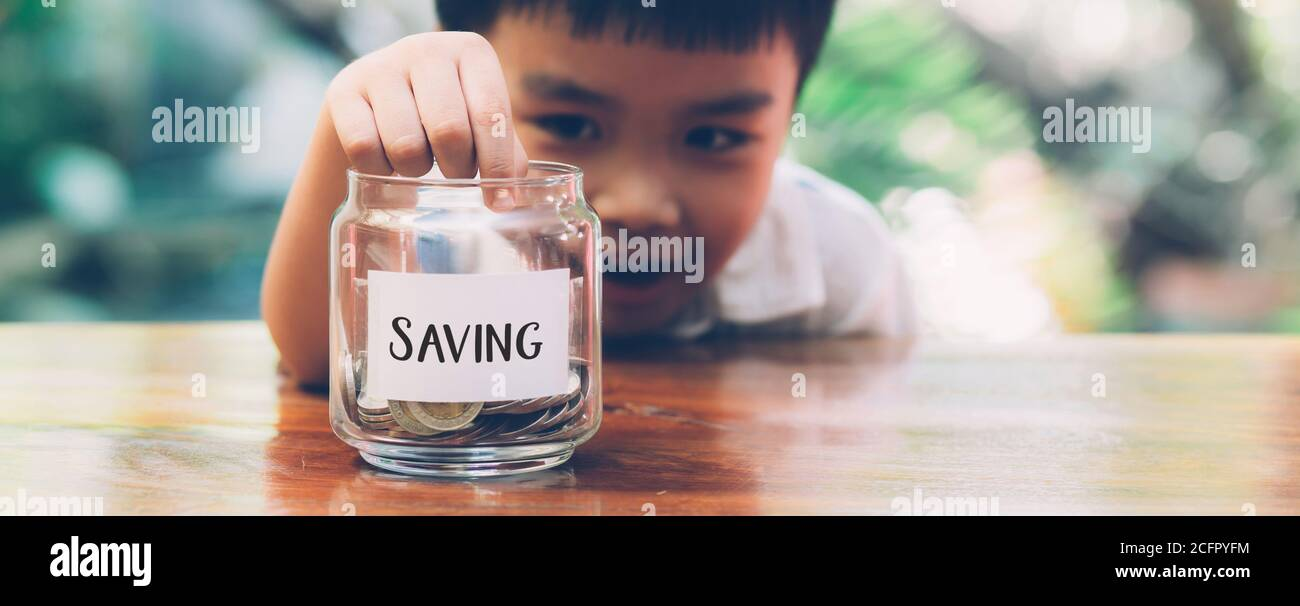 Happy asian children saving money putting coin in glass for wealth and growth of earning, finance and investment for success, boy planning and deposit Stock Photo