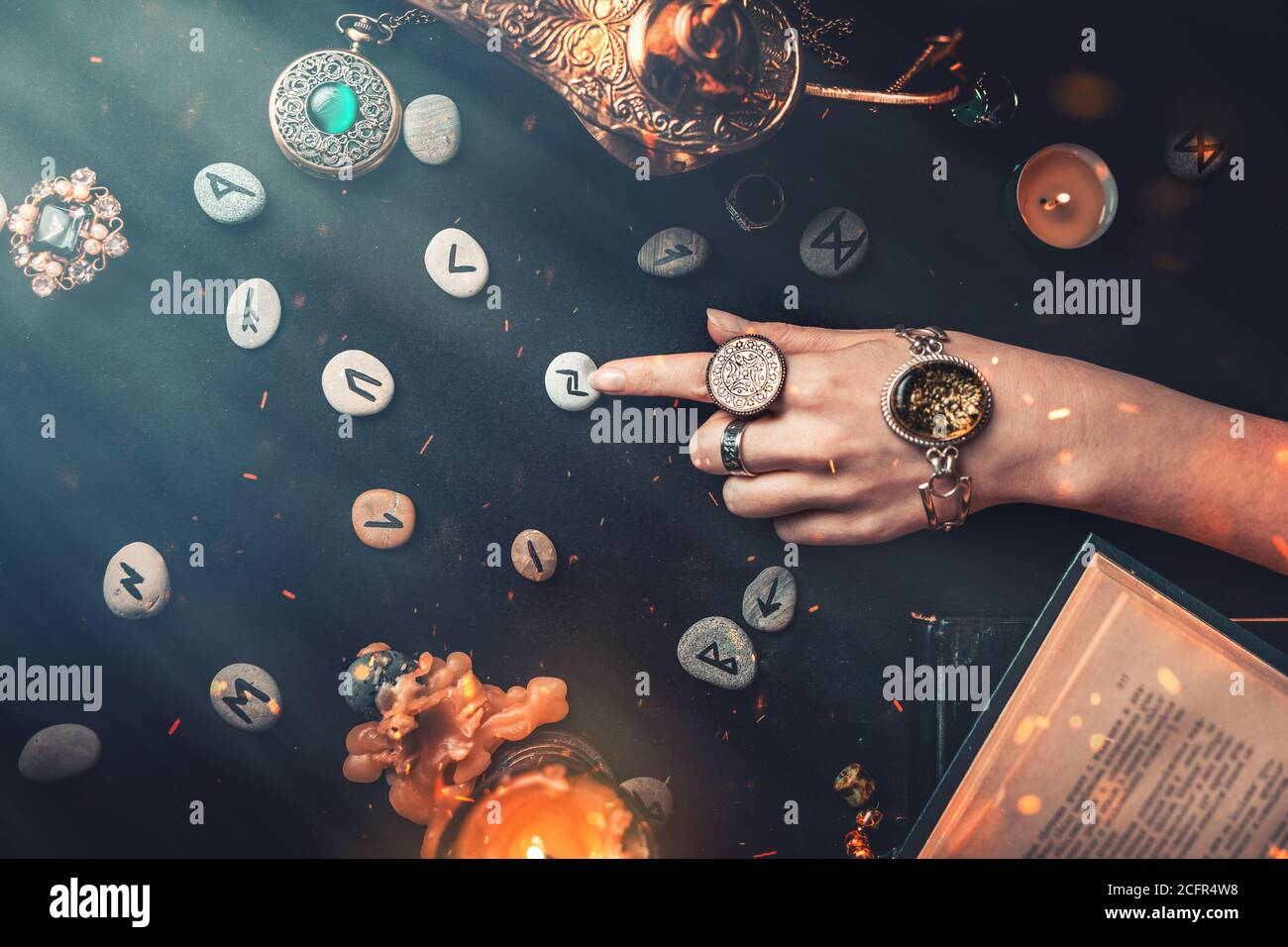 Astrology and esotericism. The witch's female hands point to the Runestone with her finger. On a black background lie fortune-telling runes, amulets, Stock Photo