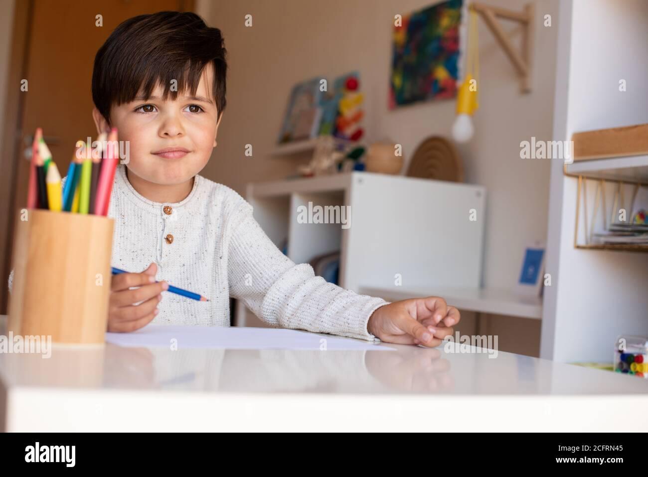 Little preschooler kid drawing with coloured pencils. Homeschooling. Learning community. Montessori school. Stock Photo