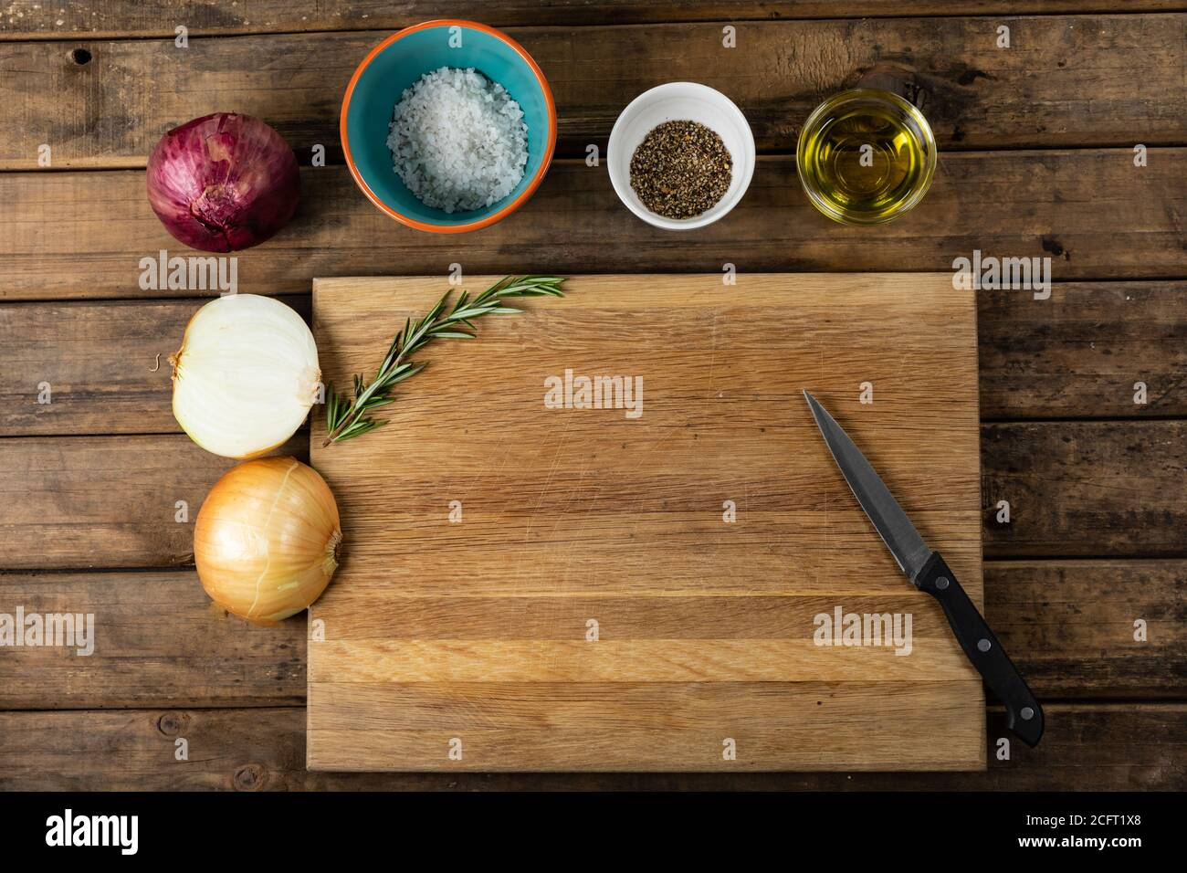 View of a wooden cutting board and knife with onion and seasonings arranged on a on a textured woode Stock Photo
