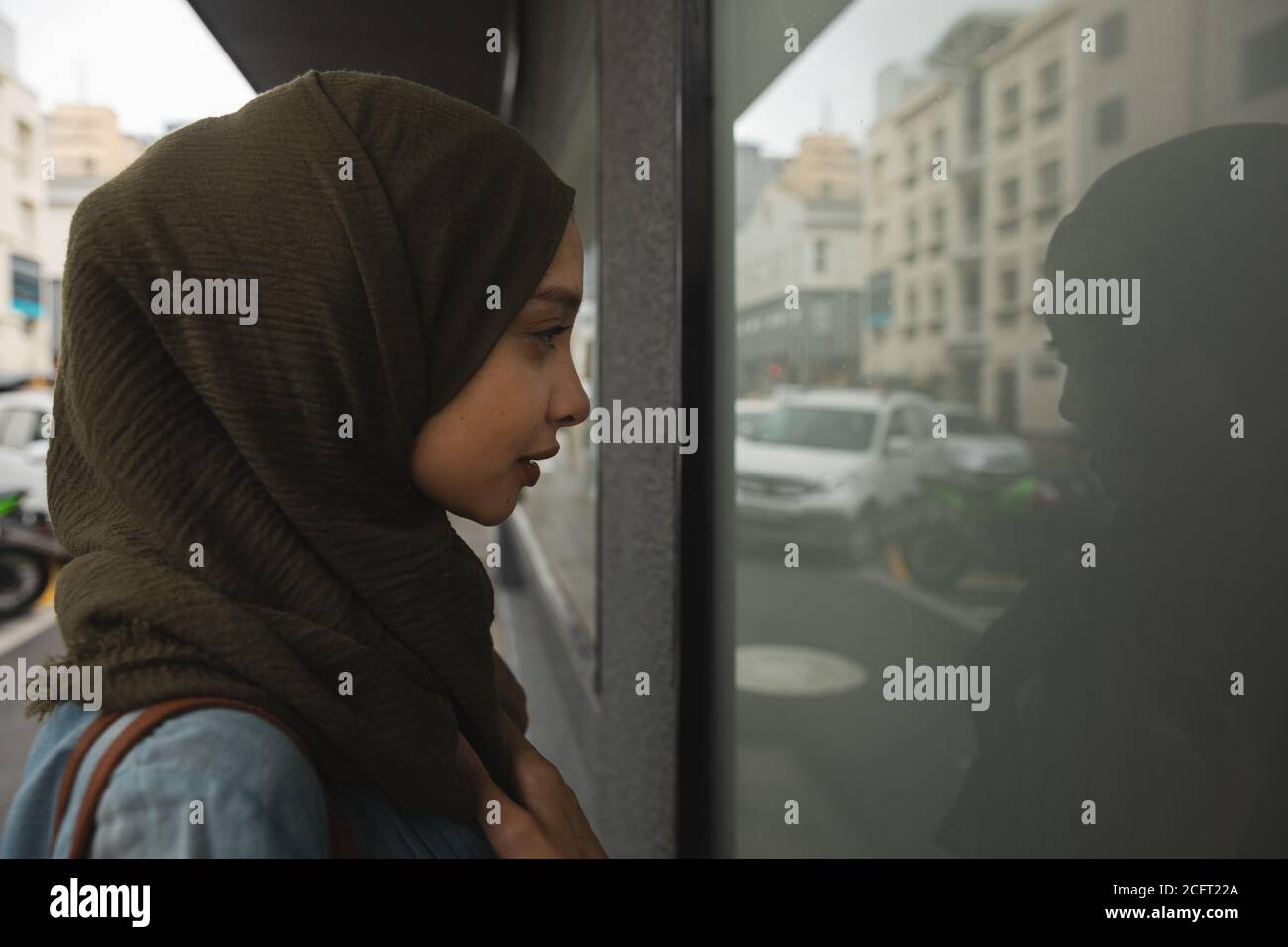 Woman in hijab looking through a shop window Stock Photo