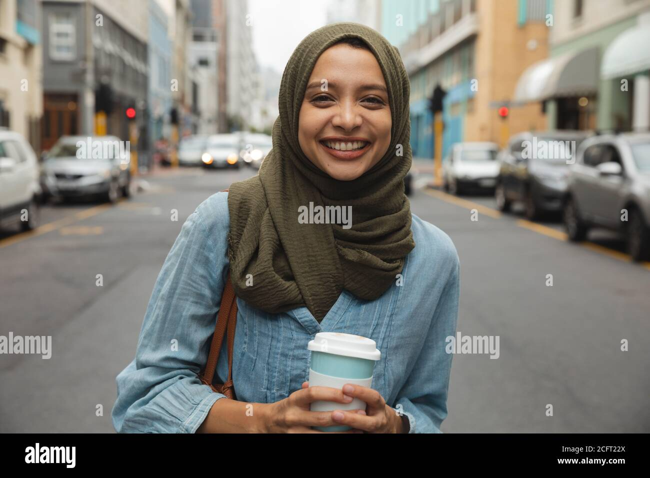 Portrait of woman in hijab with coffee cup smiling on the street Stock Photo