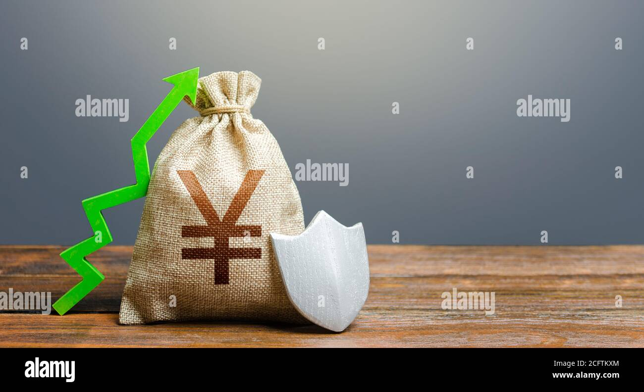 Yen Yuan money bag with a shield and a green arrow up. Safety security of investments, financial system stability. Increasing maximum amount of guaran Stock Photo