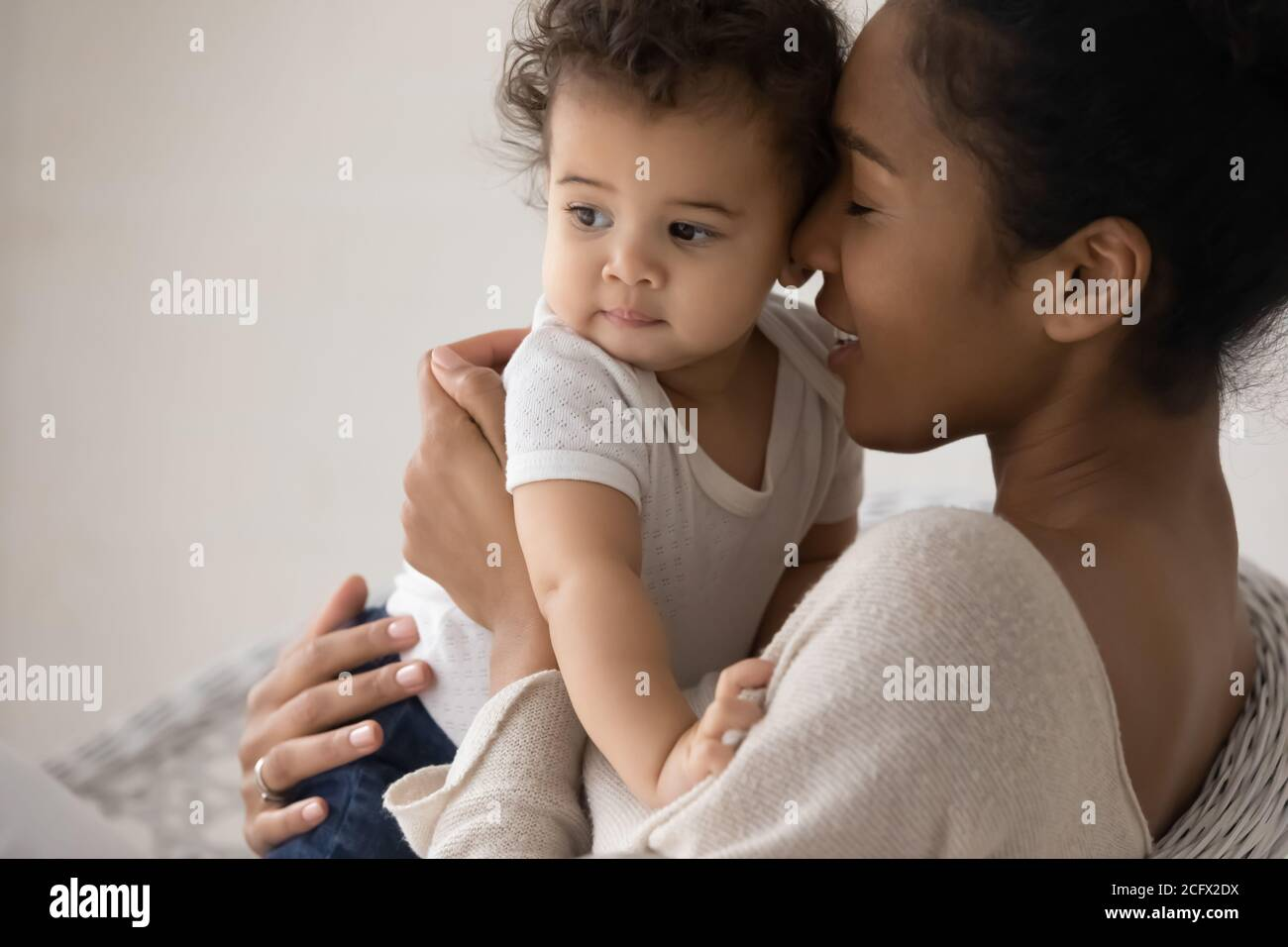 Caring young mixed race mother cuddling little biracial baby. Stock Photo