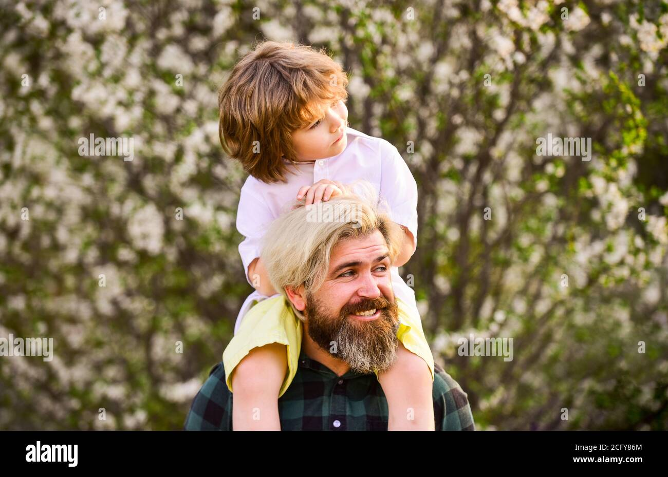 Happy family. Fathers day. Child having fun with dad. Little boy and father in nature background. Springtime. Hipster piggybacking baby. Bearded brutal man good father. Dad and son. Best dad ever. Stock Photo