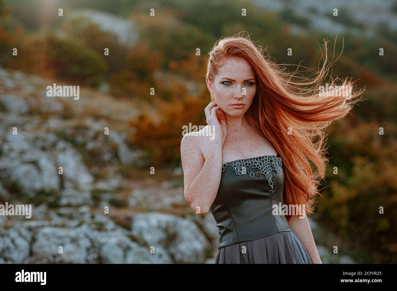 beautiful furious scandinavian warrior ginger woman in grey dress with metal chain mail. Woman is a Viking. Fantasy. Book Cover Stock Photo