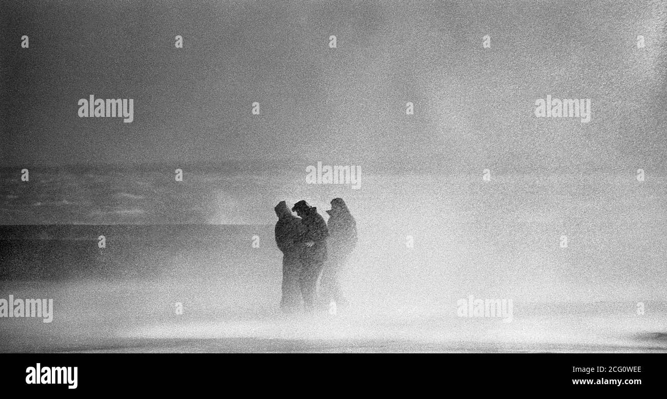 AJAXNETPHOTO. 1975. SOUTHSEA, ENGLAND. - AUTUMN STORMS - THREE YOUNG PEOPLE DRENCHED BY STORM WAVES CRASHING OVER THE SEA FRONT ALONG CLARENCE ESPLANADE. PHOTO:JONATHAN EASTLAND/AJAX REF:7526093 35 11 Stock Photo
