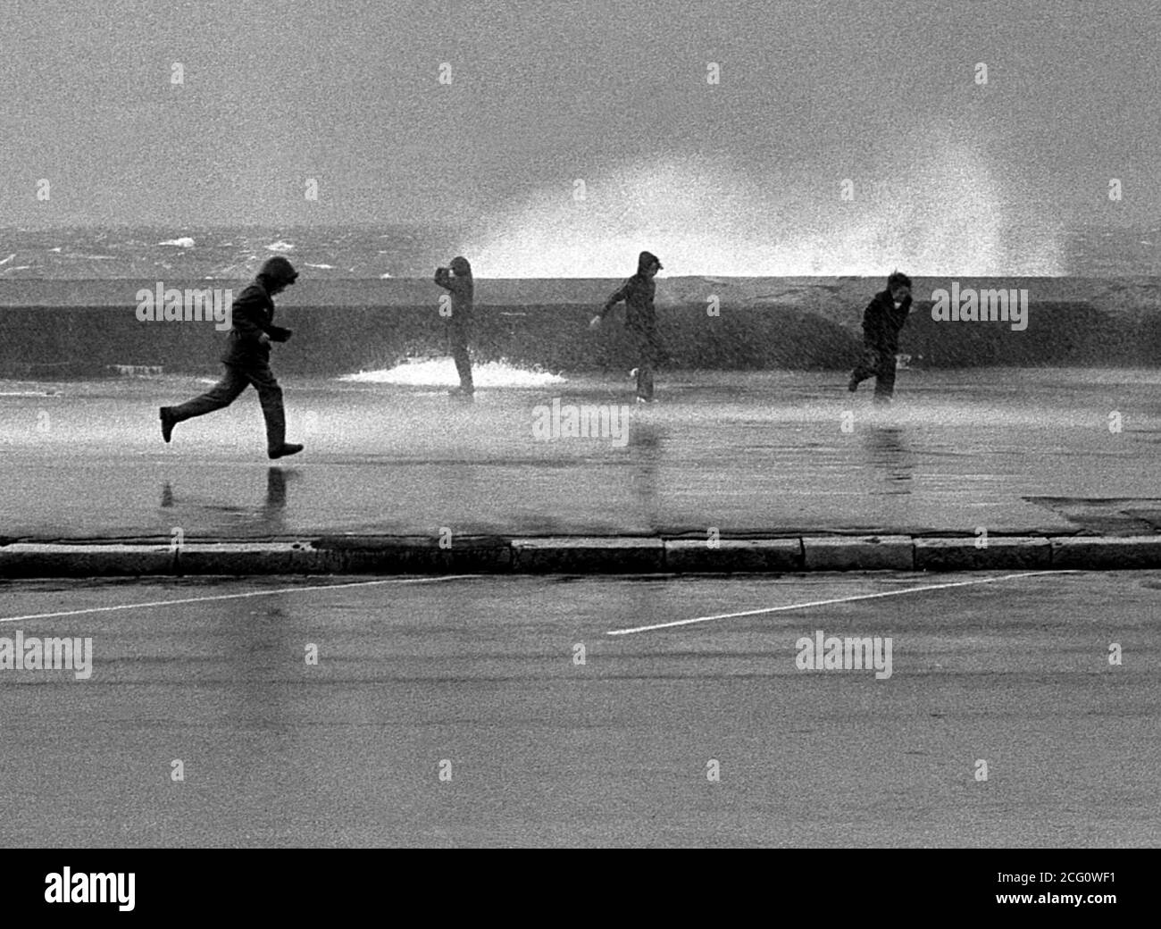 AJAXNETPHOTO. 1975. SOUTHSEA, ENGLAND. - SPRAY DODGERS - YOUNGSTERS DODGING THE SPRAY AS SEAS CRASH OVER THE PARAPIT ALONG CLARENCE ESPLANADE DURING AN AUTUMNAL GALE.PHOTO:JONATHAN EASTLAND/AJAX REF:75046 5 60 Stock Photo