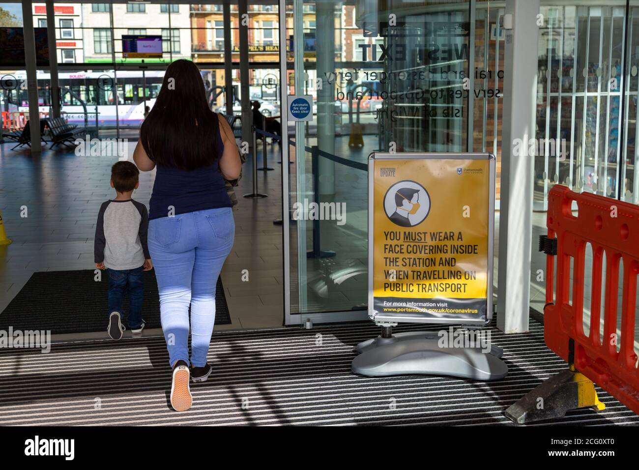 A mother and child walking past a sign showing that face masks or face coverings must be worn Stock Photo