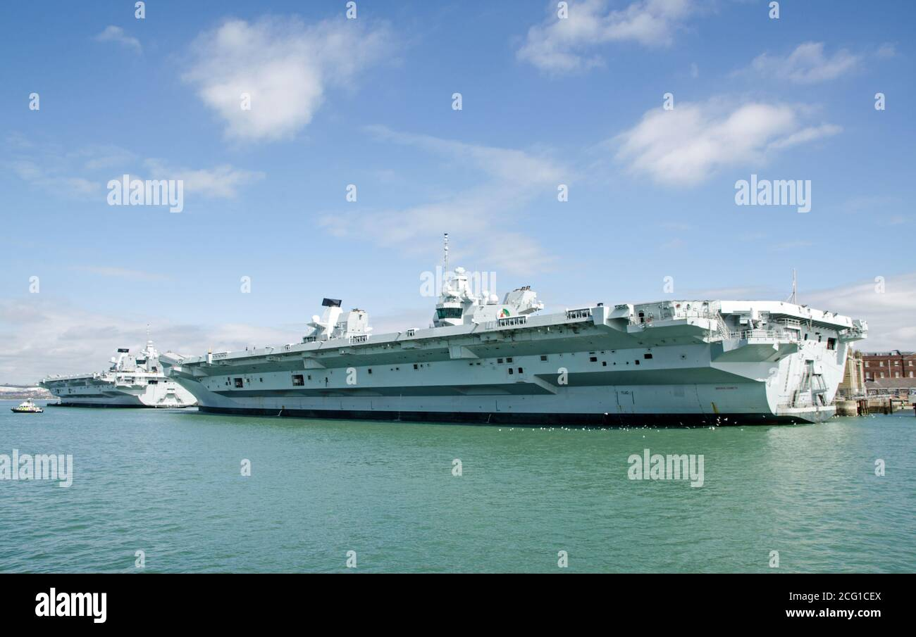 The Queen Elizabeth and Prince of Wales aircraft carriers, largest ships in the Royal Navy, moored in Portsmouth Harbour, Hampshire on a sunny afterno Stock Photo