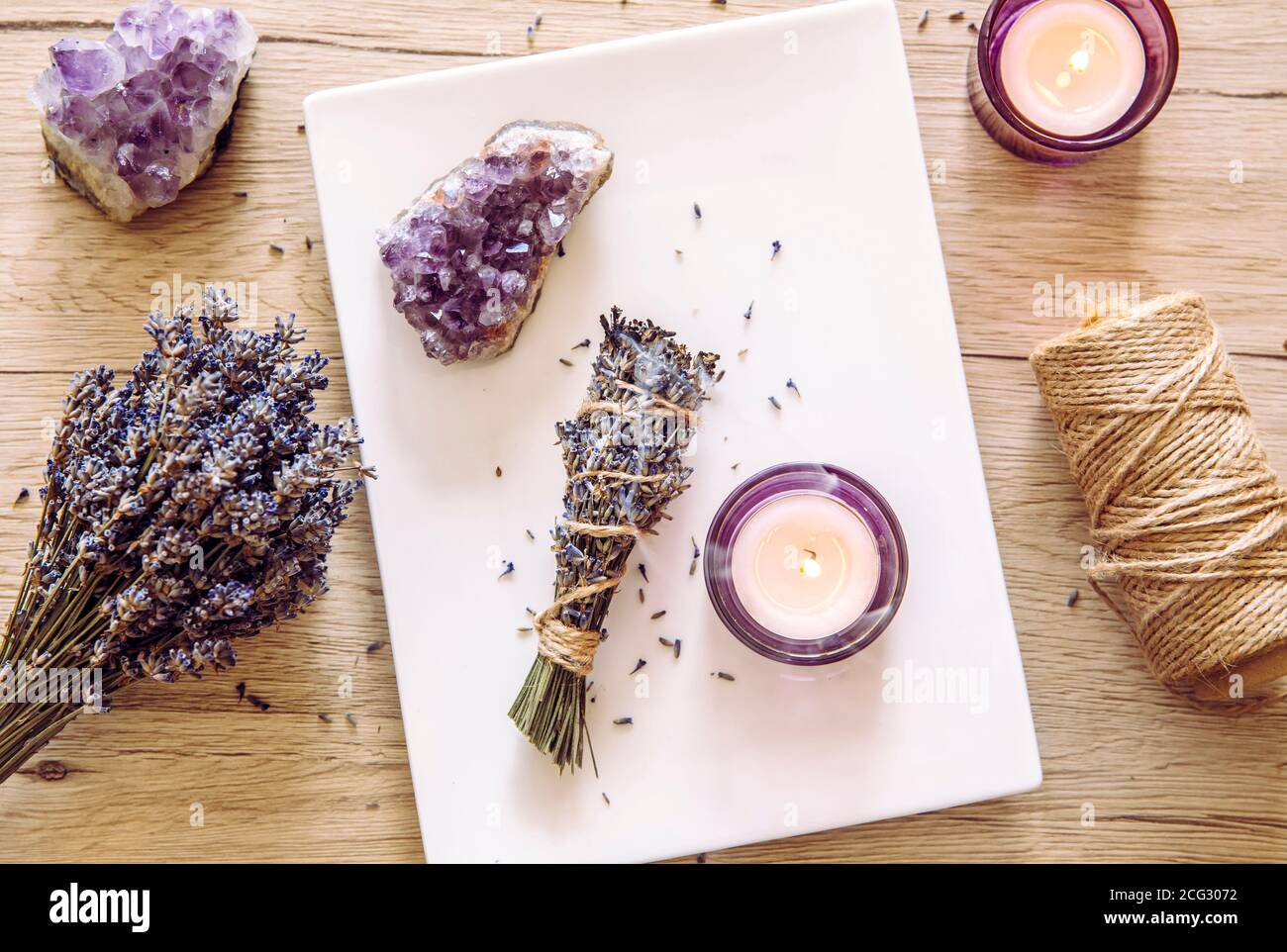 Homemade herbal lavender (lavendula) smudge stick smoldering on white plate with candles and amethyst crystal clusters for decoration. Spiritual home. Stock Photo