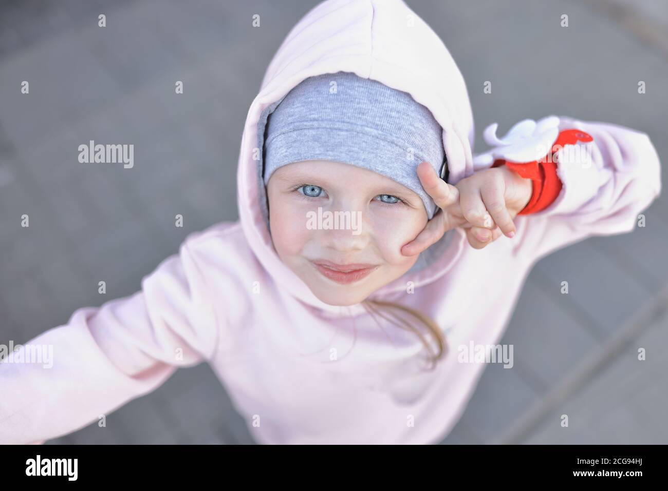 Little girl with blue eyes in warm clothes and hood looks up and greets with gesture. Stock Photo