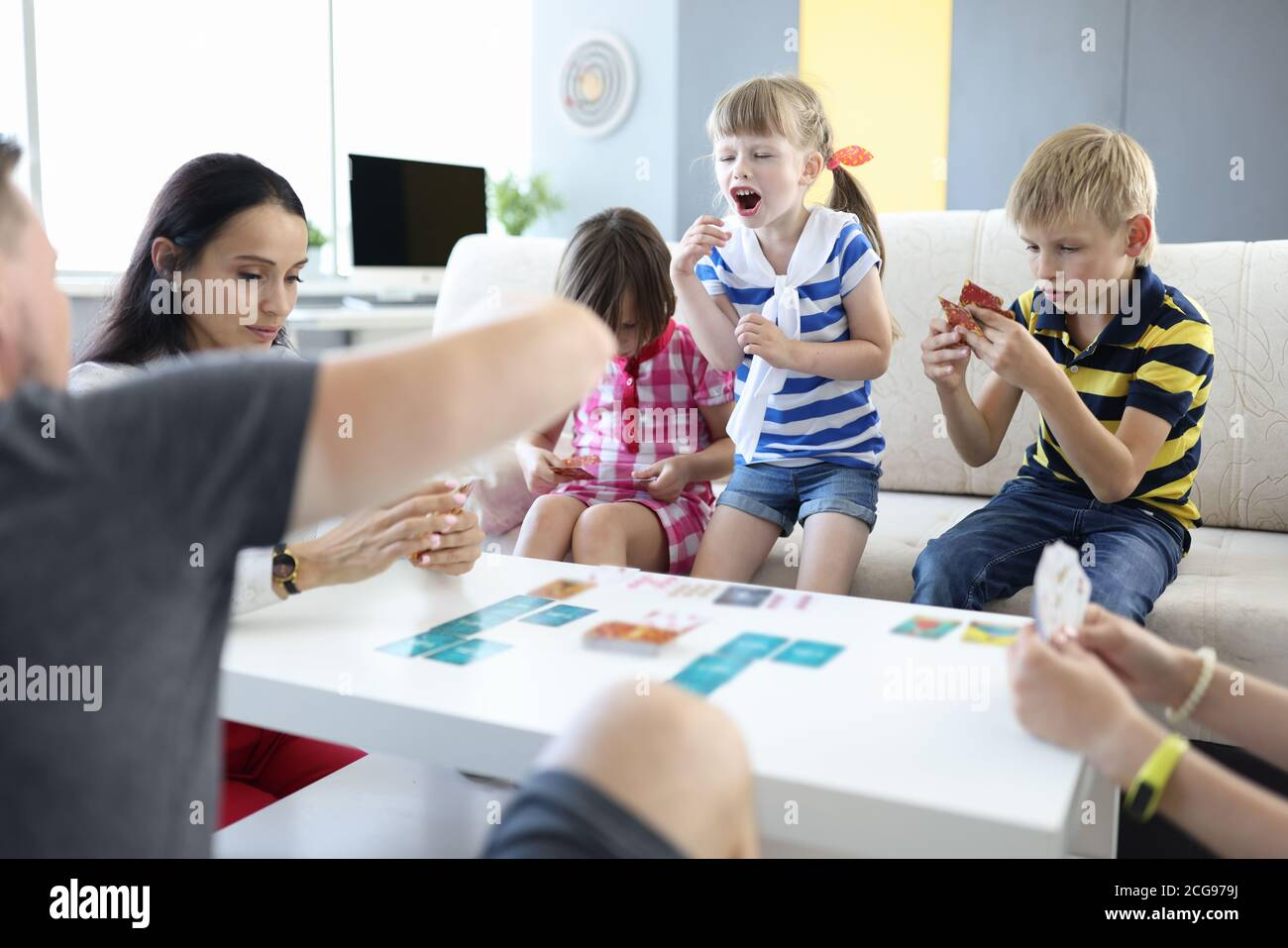Adults and children are sitting at table and holding playing cards girl stood up and shouts. Stock Photo