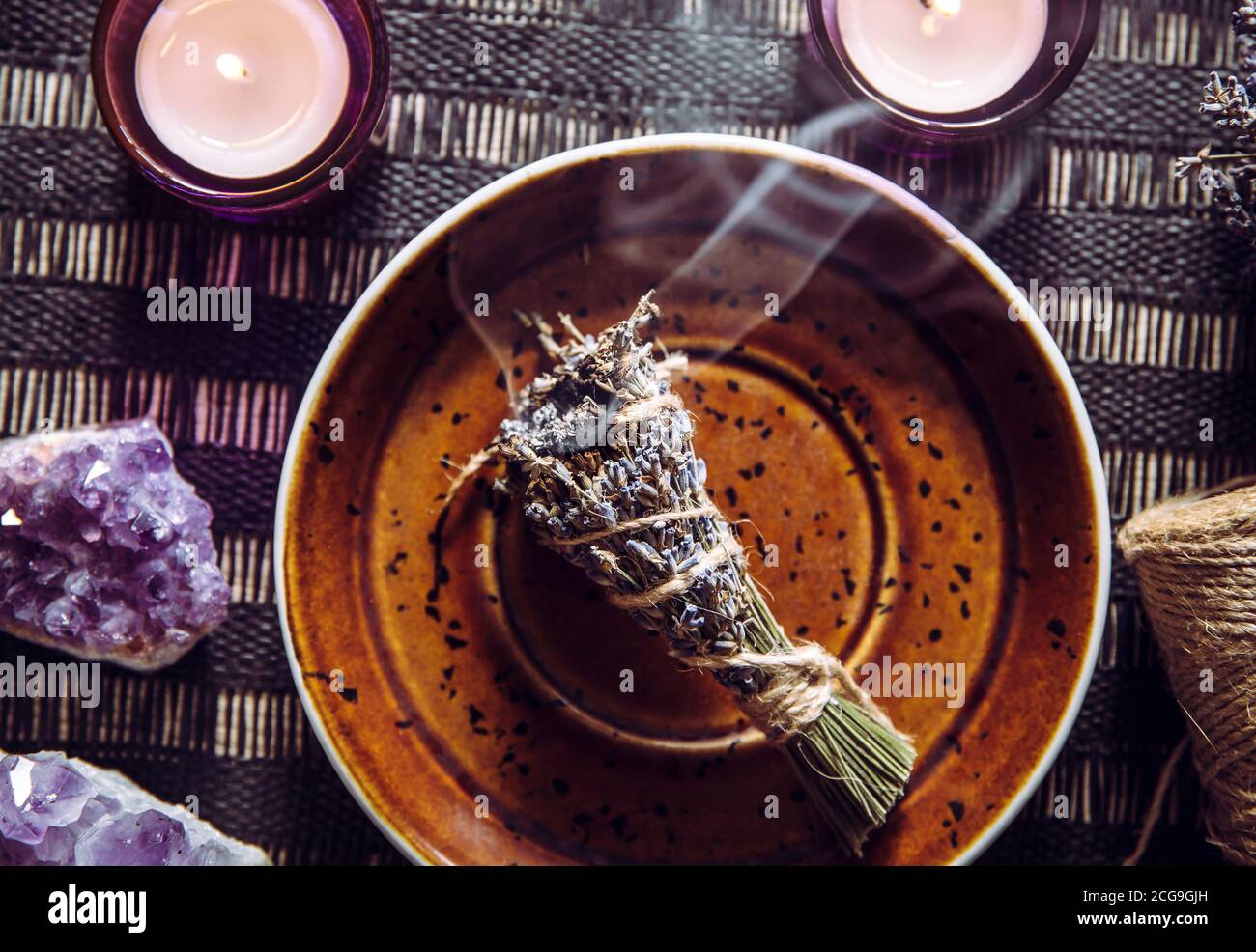 Homemade herbal lavender (lavendula) smudge stick smoldering on brown plate with candles and amethyst crystal clusters for decoration. Spiritual home Stock Photo