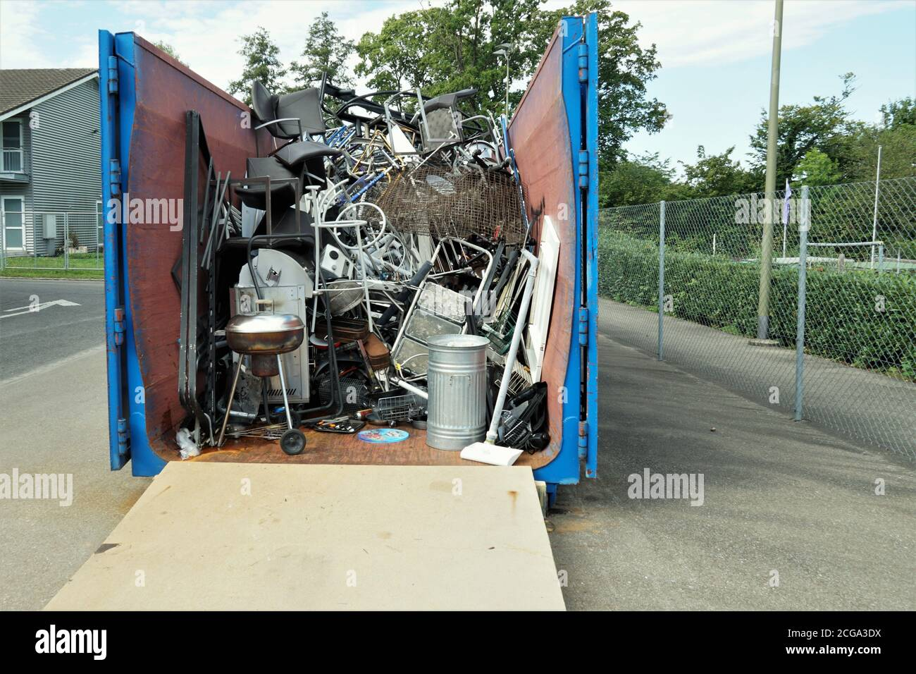 Metal waste collected in a container in a community disposal place. A public service free of charge to prevent littering the environment. Stock Photo