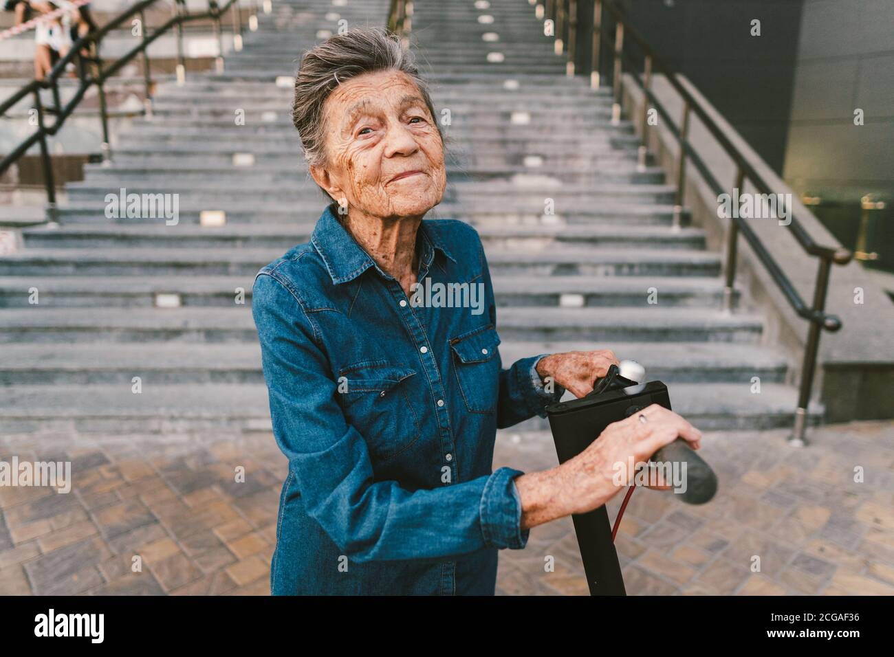 90 year old woman with gray hair, wrinkles, progressive and active uses modern electric transport scooter. Lady pensioner use eco friendly city Stock Photo