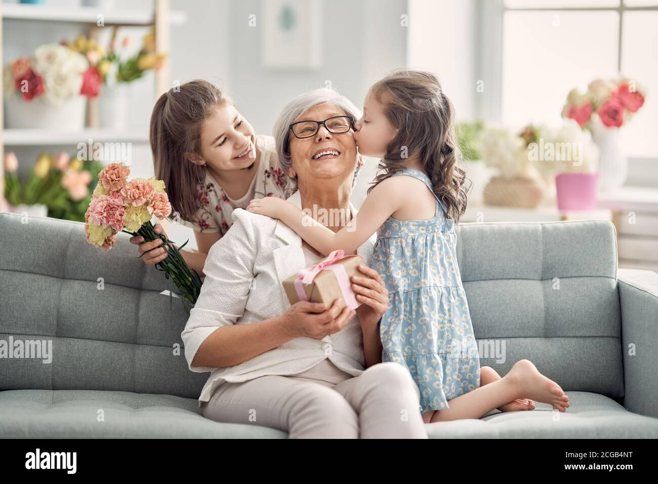 Happy mother's day! Children daughters are congratulating granny giving her flowers and gift. Grandma and girls smiling and hugging. Family holiday an Stock Photo