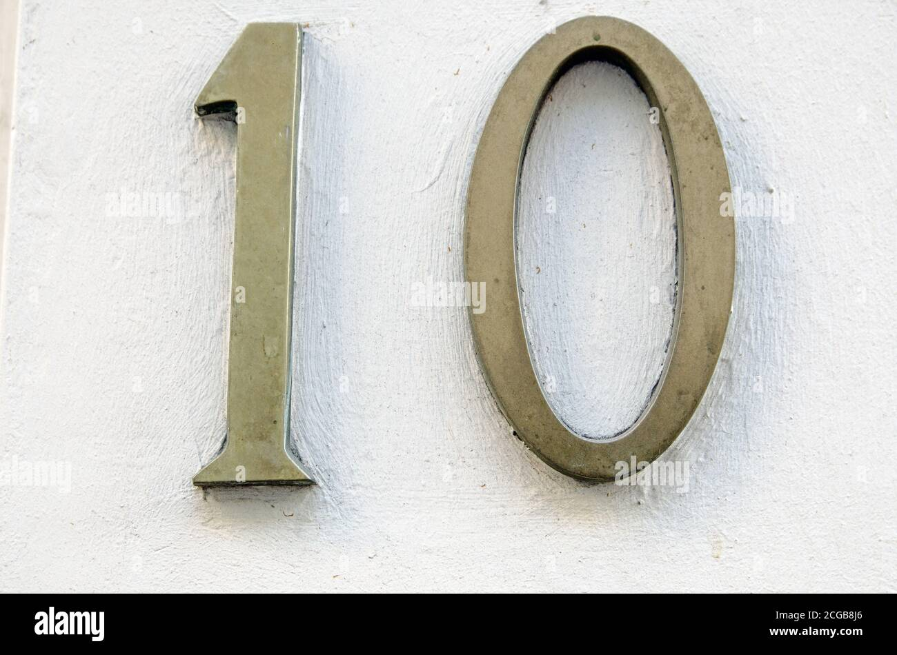 Brass figures showing the number ten on a wall in London. Stock Photo