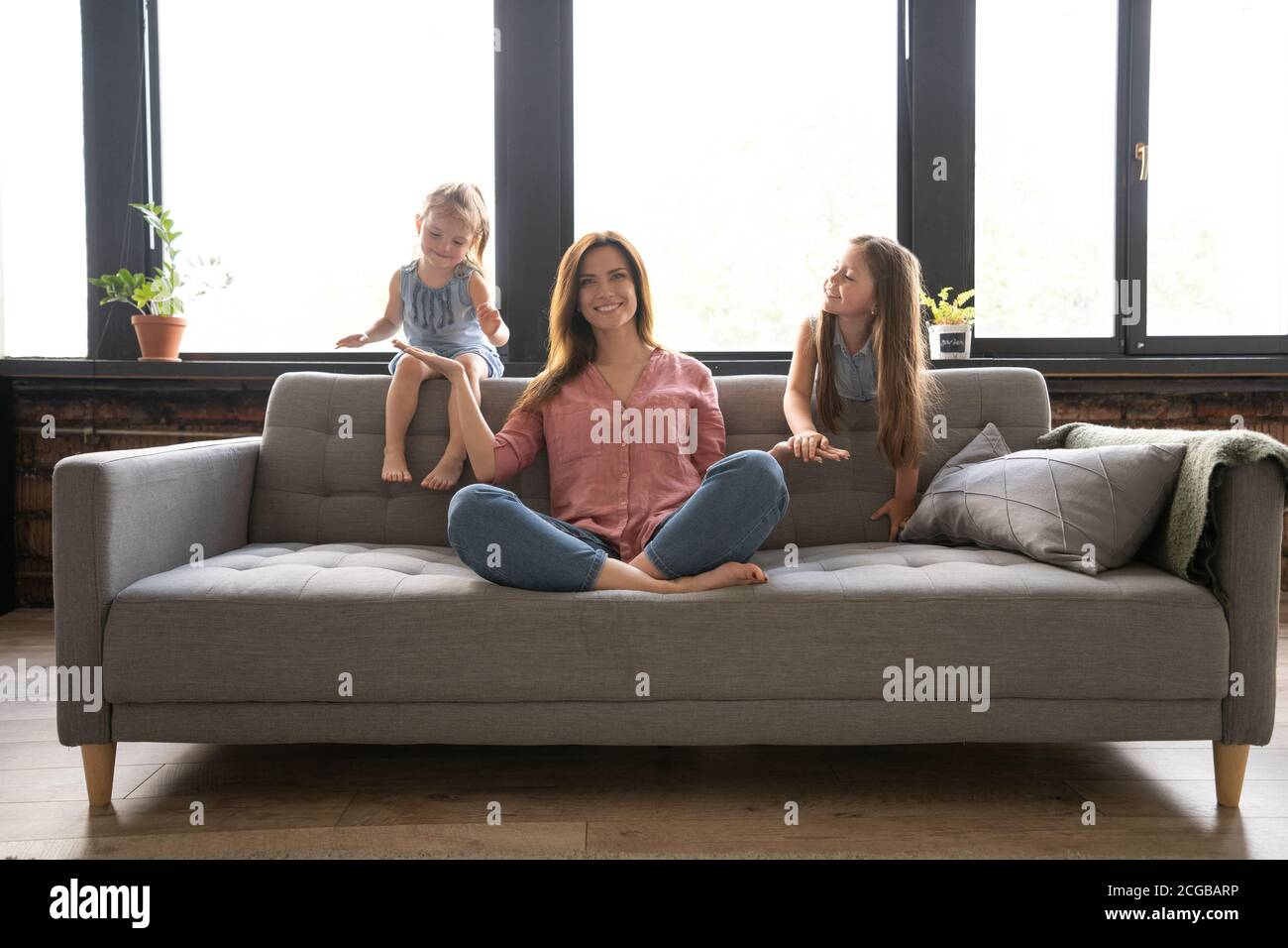 Calm woman concentrating on yoga exercises on couch at home while two noisy kids laughing, running Stock Photo