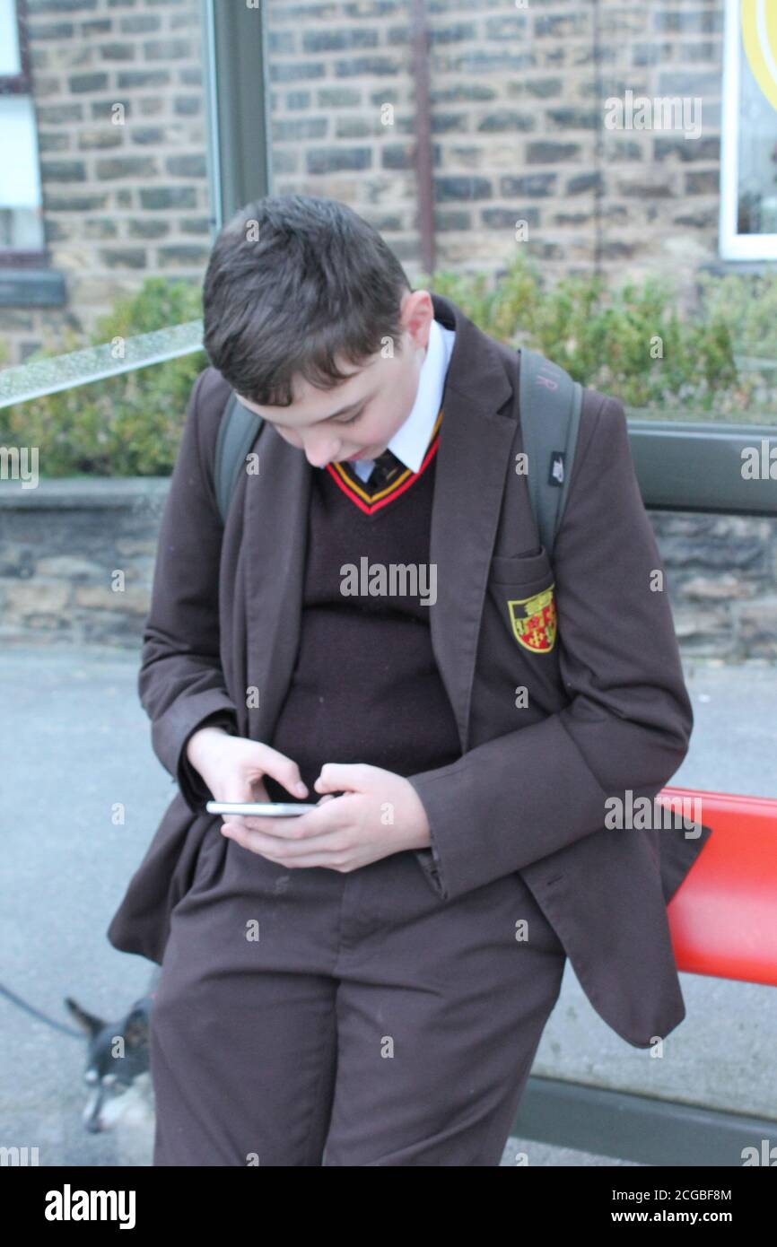 School boy in brown school uniform looking down and sat texting on a mobile phone Stock Photo
