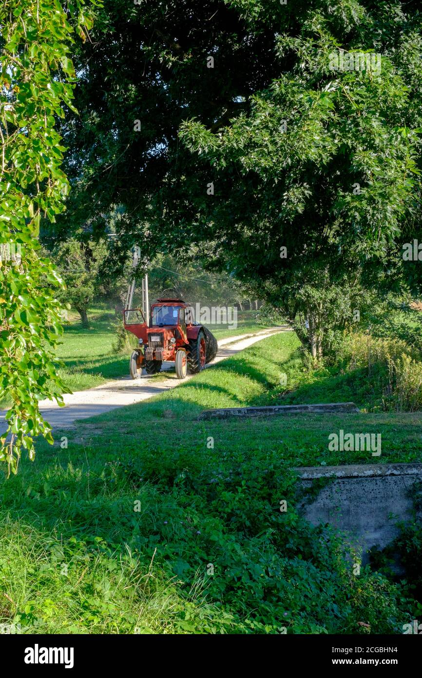 red tractor driving along rural country lane transporting large bale zala county hungary Stock Photo
