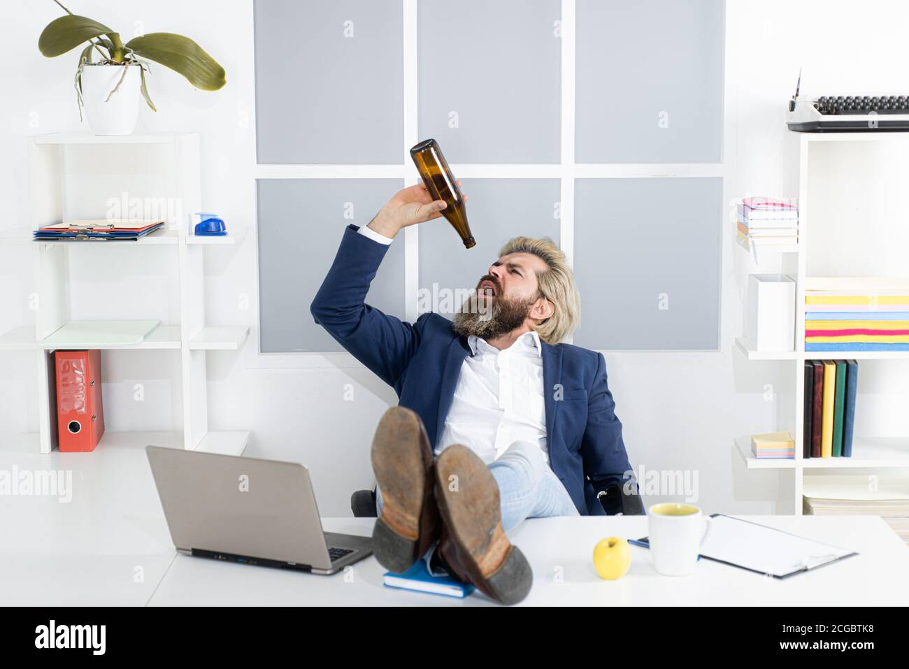 Sad office worker desperate about unfair dismissal losing job. Depressed businessman has problem at work, drinking alcohol in office. Stock Photo