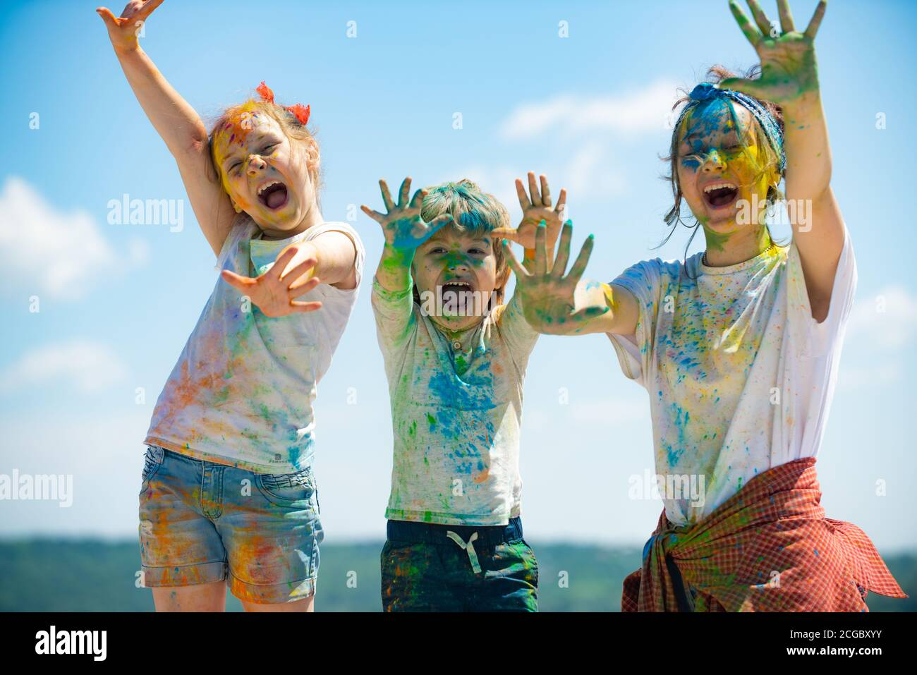 Portrait of a beautiful kids showing colorful colored hands. Happy childhood. Emotional cheerful excited children. Stock Photo